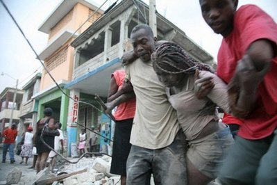 A Haitian woman is helped after being trapped in rubble in Port-au-Prince. Thousands are feared to have been killed in a massive earthquake in Haiti, President Rene Preval told a US daily Wednesday as he issued a plea for international help. (AFP/Daniel Morel)