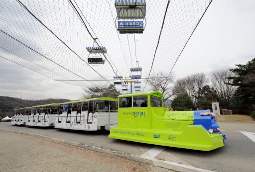 """The Online Electric Vehicle (OLEV), towing three carriages, runs along a blue line under which power strips are buried for recharging, at an amusement park in Gwacheon, south of Seoul. S.Korean researchers launched an environmentally-friendly public transport system using a """"recharging road"""" -- with a vehicle sucking power magnetically from buried electric strips. Photograph by: Jung Yeon-Je, AFP"""