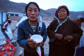 A Tibetan resident of Jiegu, Yushu County, in northwest China's Qinghai province shows all she has to eat - a bowl of barley - amid the rubble of their demolished homes on April 15, 2010. (Photo courtesy: AFP)