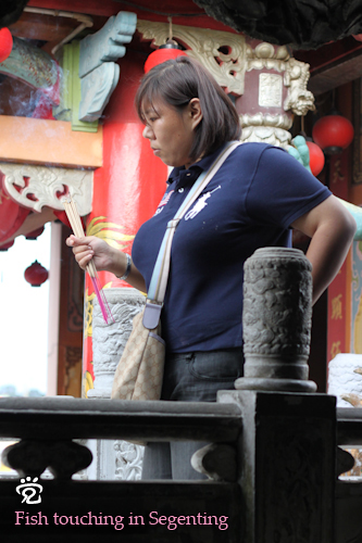 A worshipper with incense sticks at the temple