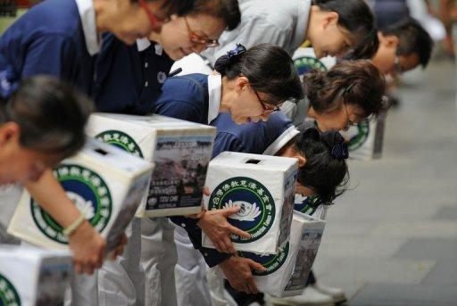 Members of the international non-profit organisation, the Buddhist Tzu Chi Foundation, bow their heads as they collect donations in Sydney (photo: AFP)