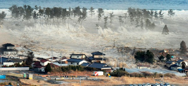 A massive tsunami engulfs a residential area in Natori, Miyagi Prefecture in northeastern Japan. (photo by Reuters/Kyodo)