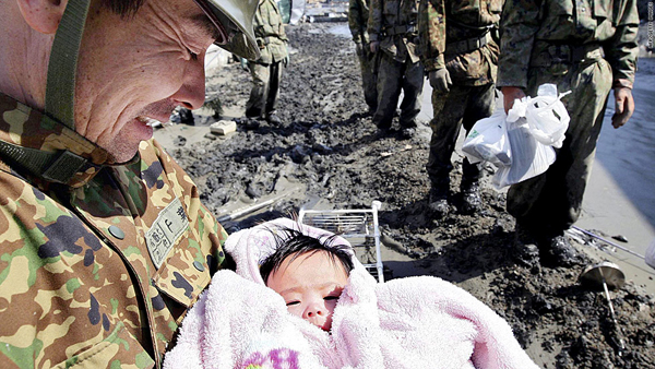 A Self Defense Forces soldier holds a 4-month-old baby in Ishinomaki city in Miyagi prefecture Monday. The child survived the tsunami with her family. (AFP/Getty photo)