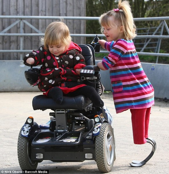 You have a go: Little Ellie is all smiles as she shows a curious Charlotte how to operate the wheelchair