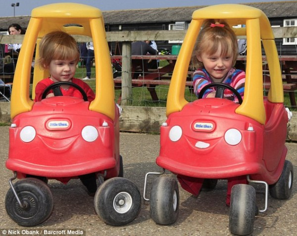 I'll race you: Charlotte (left) and Ellie giggle together as they get behind the wheels of toy cars