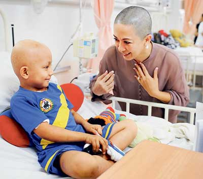 HELLO THERE: Lorna having a light moment with a patient at the child cancer unit of the Sarawak General Hospital yesterday. Earlier, Lorna had her head shaven. (Photo courtesy of Datuk Lorna Enan Muloon)