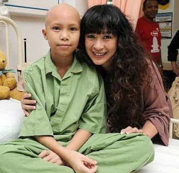 Source of courage: Lorna meeting a child in the Sarawak General Hospital before she shaved her head. (photo: The Star)