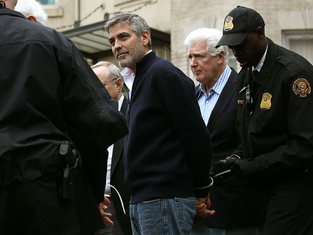 Clooney has handcuffs attached by a security official after being arrested outside the Embassy of Sudan today. (photo: Getty Images/Win McNamee)
