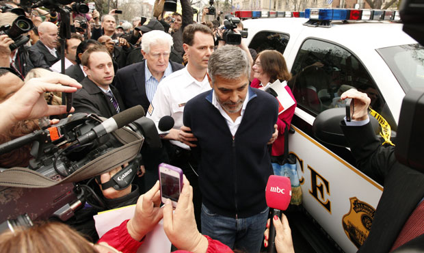 Clooney is surrounded by the media after being arrested for protesting the escalating humanitarian crisis in Sudan. (photo: REUTERS/Kevin Lamarque)
